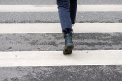 Close-up of person crosses a pedestrian crossing back view. Close-up photography. Person crosses a pedestrian crossing back view Royalty Free Stock Photos