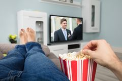 Person Watching Movie While Eating Popcorn Stock Photo
