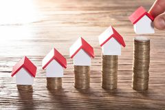 Person Placing House Models On Stacked Coins. Close-up Of A Person Hand Arranging House Models On Increasing Stacked Coins Royalty Free Stock Photography