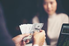 Close-up Of Person Hand Giving Money To Other Hand. Vintage filter image royalty free stock image