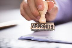 Person`s Hand Holding Approved Stamp On Document. Close-up Of A Person Hand Holding Approved Stamp On Document Over The Desk In Office stock image