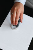 Close-up Of Person Hand Stamping Document At Desk Royalty Free Stock Photos