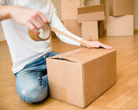 Close up of person hands packing cardboard box Stock Photo