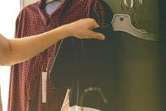 Close up person hands trying picking and choosing casual clothes in shopping dressing room royalty free stock images