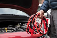 Close-up Of A Person Holding Jumper Cables royalty free stock photo