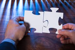 Close-up of a person joining two jigsaw pieces Royalty Free Stock Photos