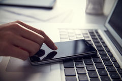 Close Up Of Person At Laptop Using Mobile Phone Stock Images