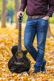 Close up person man`s hands on acoustic guitar artist musician. Close up person man`s hands on acoustic guitar in autumn park. Focus on guitar royalty free stock photos