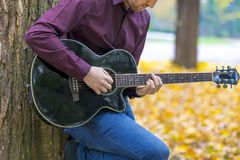 Close up person man`s hands playing acoustic guitar artist music. Ian. Focus on fingers royalty free stock image