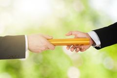 Two Businessman`s Passing A Golden Relay Baton. Close-up Of A Person Passing Golden Relay Baton To Another Person royalty free stock images