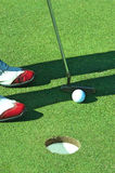 Close up of person putting golf ball on golf course Royalty Free Stock Photos