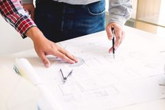 Close-up Of Person's engineer Hand Drawing Plan On Blue Print with architect equipment, Architects discussing at the table, team. Work and work flow stock photography