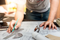 Close-up Of Person's Hand Drawing Plan On Blue Print with archit Stock Images