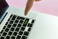 Close up person`s hand finger pushing the `sale` text on a button of laptop keyboard isolated concept v royalty free stock image