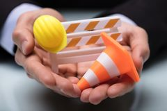Close-up Of Barricade With Traffic Cone And Hard Hat. Close-up Of Person`s Hand Holding Barricade With Traffic Cone And Hard Hat stock photo