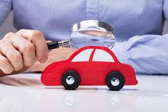 Person Looking At Car Through Magnifying Glass stock photography