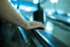 Close up person`s hand moving up on the escalator stock images