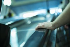 Close up person`s hand moving up on the escalator royalty free stock photography