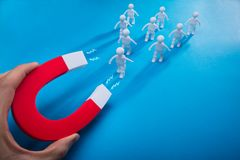 Person Pulling Human Figures With Horseshoe Magnet. Close-up Of A Person`s Hand Pulling Human Figures With Horseshoe Magnet On Blue Background stock images