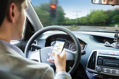 Person Sending Text Message By Mobile Phone While Driving Car stock image
