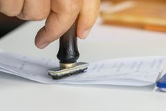 Close-up Of Person`s Hand Stamping On Approved Application Form or Notary public in office documents for signing approval. stock images