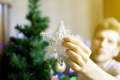 Close up person`s hands putting white decoration star on top of christmass tree f stock photography