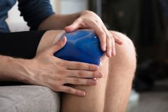 Person Sitting And Applying Ice Gel Pack On Knee. Close-up Of A Person Sitting And Applying Ice Gel Pack On An Injured Knee royalty free stock image