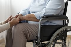 Close-up of person supporting paralysed senior woman on the wheelchair royalty free stock image