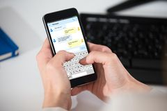 Person Sending Messages On Cell Phone. Close-up Of A Person Texting Messages On Cell Phone Royalty Free Stock Images