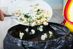 Person Throwing Cooked Pasta In Trash Bin. Close-up Of A Person Throwing The Leftover Pasta Into The Trash Bin Royalty Free Stock Image