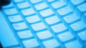 Close up of person typing on keyboard under blue light. A close up shot of a person typing on a white keyboard under a blue tinted light. HD 1080 stock footage