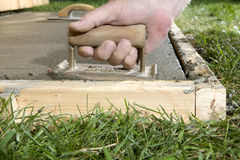 Close up of person using concrete edging tool. A close up of a man using a concrete edging tool on wet cement slab with timber form work in a backyard, DIY Royalty Free Stock Images