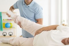 Personal physiotherapist rehabilitating joints. Close-up of personal physiotherapist rehabilitating senior woman`s joints after hip reconstruction Royalty Free Stock Photo