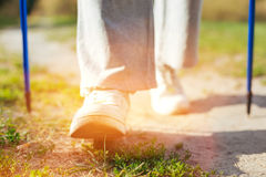 Close up of a persons feet making a step. Only forward. Close up of a persons feet making a step while doing Nordic walking in the park stock image