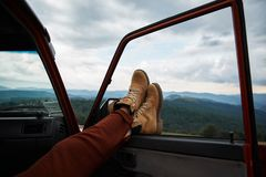 Close up of persons feet on the off-road car window. Close up of feet of a relaxed traveler holding them on the window while enjoying mountains view stock images