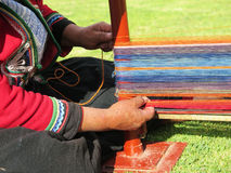Close up of Peruvian lady in authentic dress spinning yarn by ha Royalty Free Stock Photo