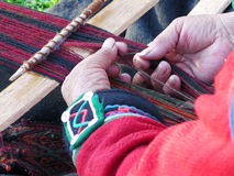 Close up of Peruvian lady in authentic dress spinning yarn by ha Royalty Free Stock Photography