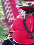 Close up of Peruvian lady in authentic dress spinning yarn by ha Stock Photos