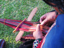 Close up of Peruvian lady in authentic dress spinning yarn by ha Stock Photo