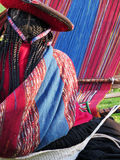 Close up of Peruvian lady in authentic dress spinning yarn by ha Royalty Free Stock Images