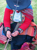 Close up of Peruvian lady in authentic dress spinning yarn by ha Stock Photography