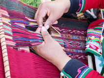 Close up of Peruvian lady in authentic dress spinning yarn by ha Stock Images