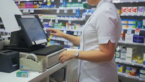 Close up of a pharmacist processing a transaction at a cash register in a pharmacy. Close up of a pharmacist processing a transaction at a cash register in an stock video footage
