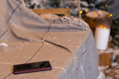 Close up of a phone in a swing with a blanket in a snow-covered Stock Photography