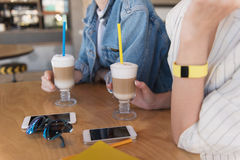 Close up of a phones on a table while girls holding their drinks Stock Image