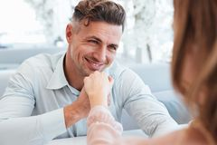 Close up photo of adult handsome man smiling, and holding hand o Stock Photos
