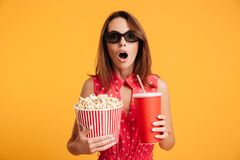 Close-up photo of amazed beautiful young woman in 3d glasses hol. Ding cola and popcorn and looking camera, isolated on yellow background Royalty Free Stock Image