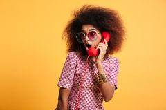 Close-up photo of amazed retro girl with afro hairstyle holding. Retro phone,  over yellow background Stock Photo