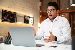 Close-up photo of amazed young businessman in glasses and white. Shirt looking at laptop screen in office Royalty Free Stock Photo