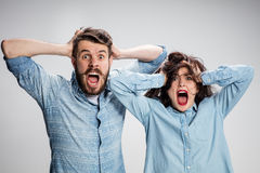 Close up photo of angry man and woman touching their heads. Close up photo of angry men and women touching their heads and screaming Stock Photography